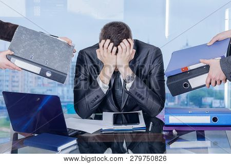 A Businessman Is Sitting At His Working Place In The Office Closing His Face With Hands In Working S