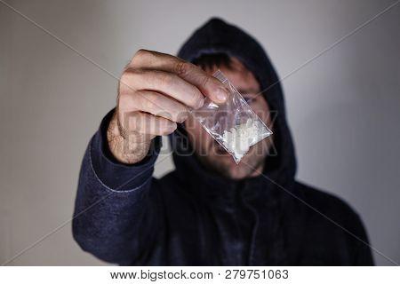 Male Dealer Holding Drugs In Plastic Bag Near Wall