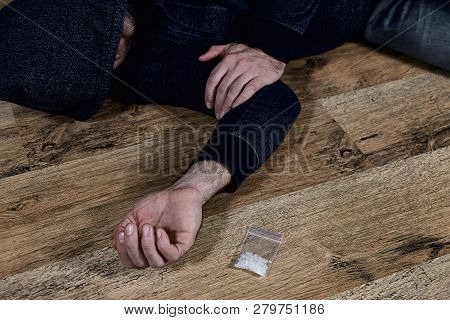 A Man Is A Drug Addict Using Drugs Lying On The Floor. The Concept Of Anti Drugs.