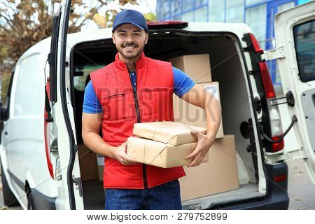 Young Courier With Parcels Near Delivery Van Outdoors