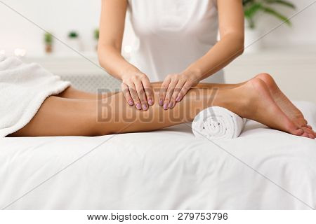 Massage Therapist Massaging Woman Calves In Spa Center, Side View