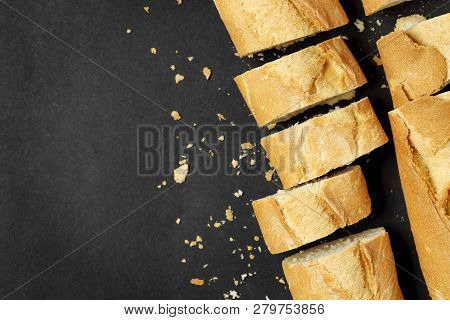 Top View Of Sliced Baguette On Black With Copy Space