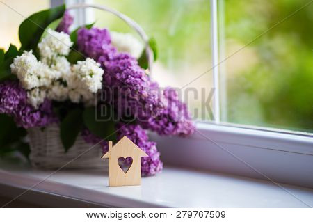 Wooden House With Hole In Form Of Heart And Tender Bouquet Of Beautiful Lilac In White Basket Near W