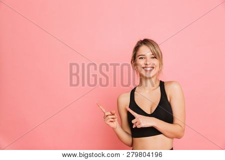 Image of a beautiful young sports blonde woman make fitness exercises isolated posing pointing.