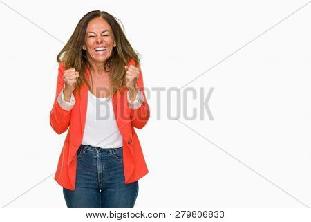 Beautiful middle age business adult woman over isolated background excited for success with arms raised celebrating victory smiling. Winner concept.