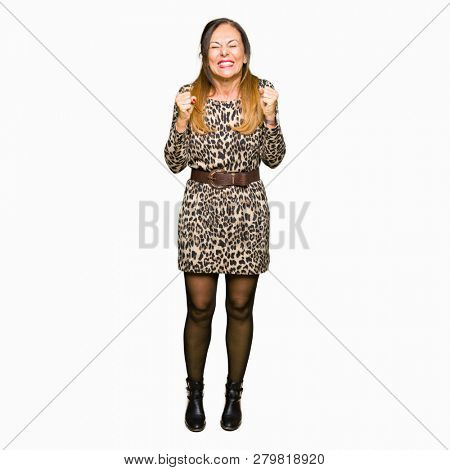 Beautiful middle age woman wearing leopard animal print dress excited for success with arms raised celebrating victory smiling. Winner concept.