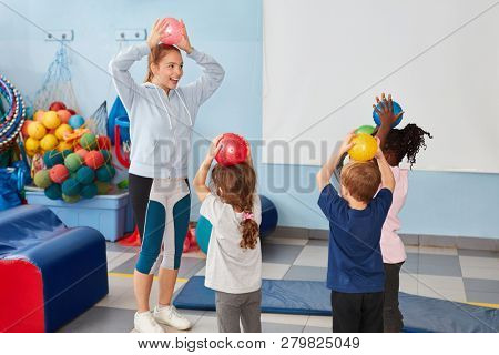 Children play with balls in the gym together with kindergarten teacher or sports teacher