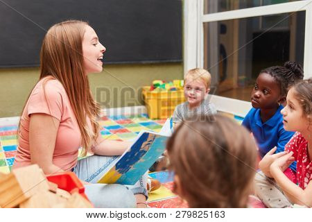 Group of children and kindergarten teacher reading a fairytale book in the day-care center