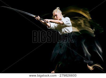 one bodokas fighters woman practicing Iaido  Kenjutsu  studio shot isolated on black background