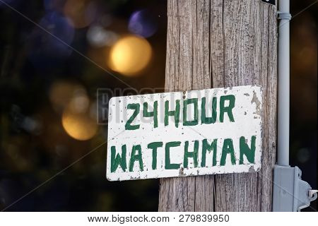 A rustic hand painted sign for a 24 hour watchman.