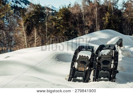 Snowshoes Against The Backdrop Of Snow-capped Mountains And Forests. Winter Mountain Tourism