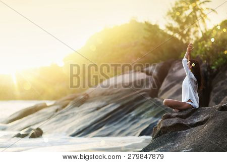 Woman Yoga Meditates on a Rock on the Ocean Beach in the Sunlight