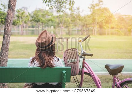 Young Woman With Vintage Bicycle Sitting And Relaxing In The Park