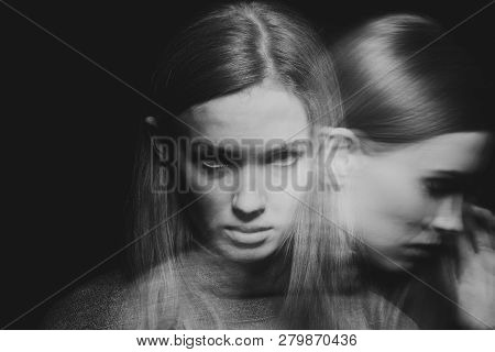 Blurred black and white picture of young beautiful redhead girl with obsessive compulsive disorder covering her mouth and closing her eyes poster