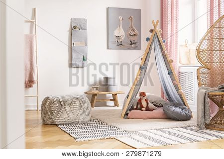 Patterned Pouf On Carpet Next To Tent With Cushions In White Kid's Room Interior With Poster. Real P