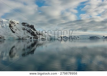 The Landscape Of The Coast Of Antarctica, Mountains Covered With Snow And Ice-cold Ocean.