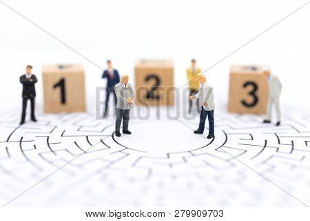 Miniature people : Businessman standing on wooden blocks with sequential numbers. Image use for business concept. poster