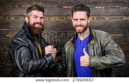 Have Agreed. Brutal Bearded Men Wear Leather Jackets Shaking Hands. Strong Handshake. Friendship Of