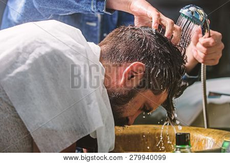 Man bearded client of hipster barbershop. Barbershop concept. Barbers hands washing hair of bearded hipster. Man with beard and mustache with towel on shoulders, male hands with shower on background poster