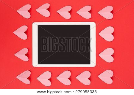 Flat Lay Of Touchpad With Blank Screen On Red Background With Paper Cut Hearts