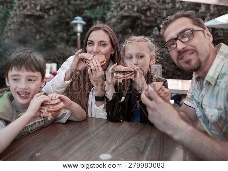 modern family eating hamburgers sitting at a table in a street restaurant