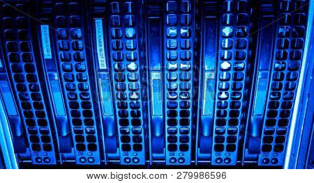 close-up of Data center with hard drives in a row, blue tint