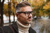 Photo of bearded man 30s wearing eyeglasses looking at camera while walking outdoor through autumn park poster