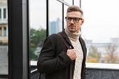Portrait of stylish man 30s wearing eyeglasses walking through city street near the building poster