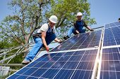 Two young technicians installing heavy solar photo voltaic panel on tall steel platform on green tree background. Exterior solar panel voltaic system installation, dangerous job concept. poster