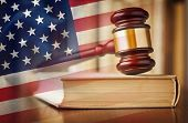 Judges gavel with law book in court and US flag in a concept of judgement, prosecution, the law and judiciary in the United States of America poster
