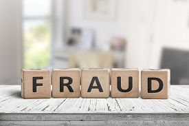Fraud Sign Made Of Wooden Blocks On A White Desk In A Bright Room