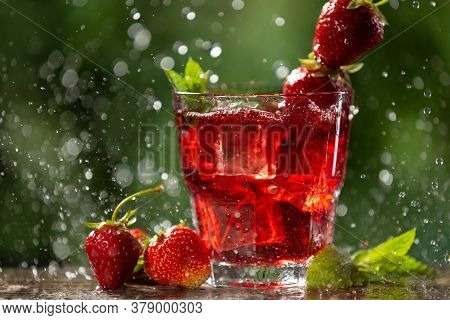 In A Glass A Red Drink With Strawberries, Mint And Ice Cubes, In Backlight, Water Drops And Splashes