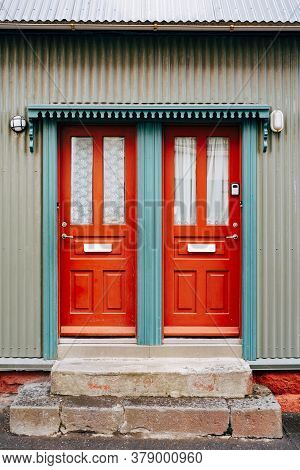 Two Orange Entrance Doors With Glass And Curtains In A Blue Doorway.