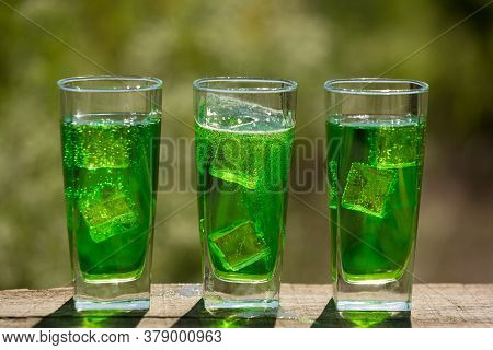 Three Glasses With An Exotic Green Carbonated Drink With Ice On The Board, Against A Background Of G