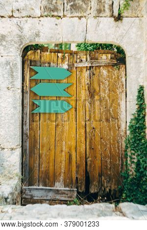 An Old Wooden Gate With Metal Pointers In The Oval Opening Of The Stone Wall.