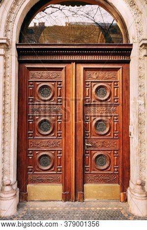 Wooden Doors With Round Windows And Hand Carved Patterns.