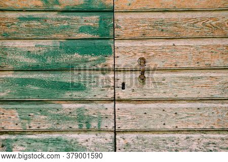 Close-up Of A Wood Entrance With Green Paint Strokes And A Metal Doorknob.