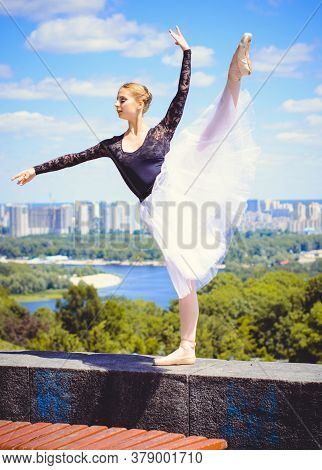 Young Woman In White Tutu Dancing In The Green Landscape. Beautiful Ballerina Showing Classic Ballet