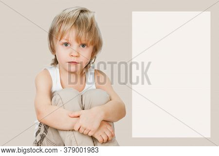 Serious Young Child Sitting On Abalone Gray Background With Copyspace