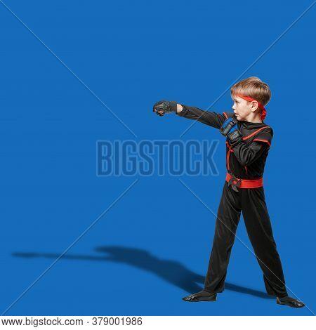 Young Boy In Kimono Practicing Taekwondo And Making Hit