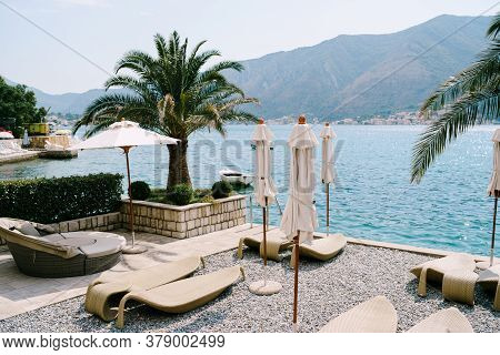 Plastic Beach Loungers On A Pebble Beach. Kotor Bay In Montenegro, The City Of Dobrota. Under The Br
