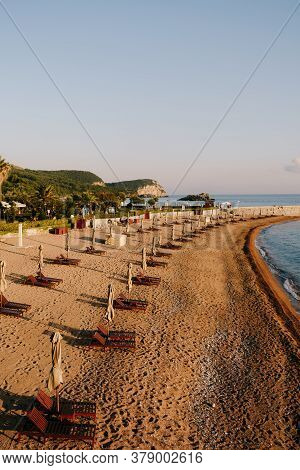 Wooden Loungers With Beach Umbrellas On A Sandy Beach In Montenegro, Near The Island Of Sveti Stefan