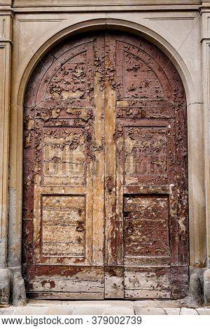 An Old Wooden Brown Door With Peeling Paint In The Oval Door Between The Columns