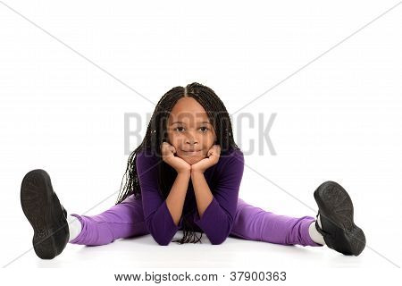 Smiling young black girl leaning on elbows
