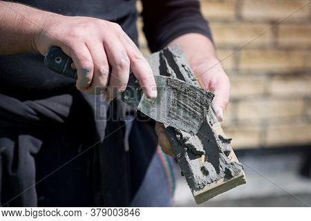 Man Applies Glue With A Spatula On A Decorative Facing Brick, View Close Up. Construction Work, Proc