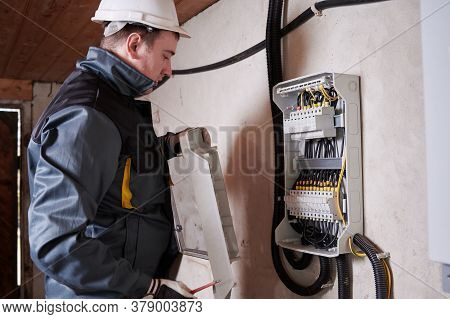 Electrical Engineer In Work Uniform Checking Electric Box With Wires And Power Fuse Switches. Man Te