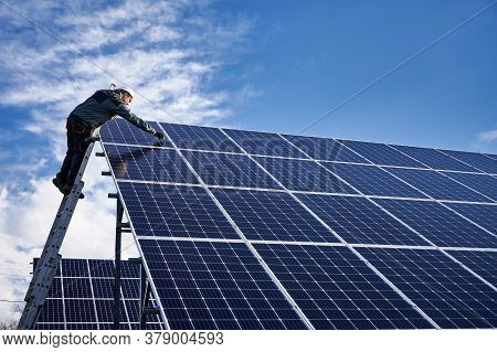 Male Worker In White Safety Helmet Standing On Ladder And Repairing Photovoltaic Solar Panel Station