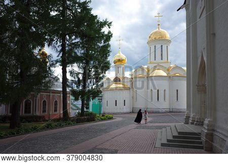 Sergiyev Posad, Russia - June 25, 2019: Trinity cathedral in the Trinity Lavra of St. Sergius, Holy Father in black clothes and woman go to old Russian church under grey sky