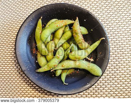 Edamame Beans In Salt And Spices. Popular Russian Snack Of Green Beans In A Black Round Bowl On The