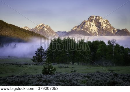 A Layer Of Fog Rolls In On A Meadow With The Mt Moran Peak Rising Above It In Grand Teton National P